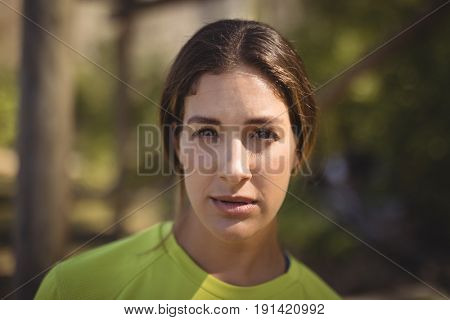 Portrait of confident woman standing in boot camp during obstacle course