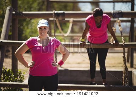 Portrait of happy woman standing with hands on hip during obstacle course in boot camp