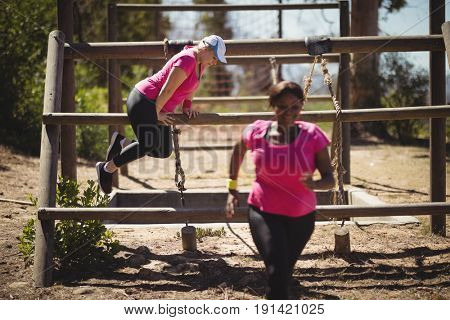 Women exercising during obstacle course in boot camp