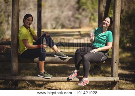 Portrait of happy friends relaxing on obstacle during obstacle course in boot camp