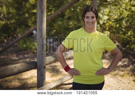 Portrait of confident woman standing with arms crossed during obstacle course in boot camp