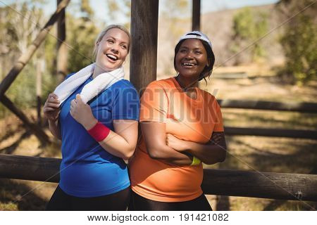 Happy friends standing with arms crossed during obstacle course in boot camp