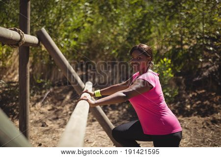 Portrait of happy woman exercising on outdoor equipment during obstacle course in boot camp