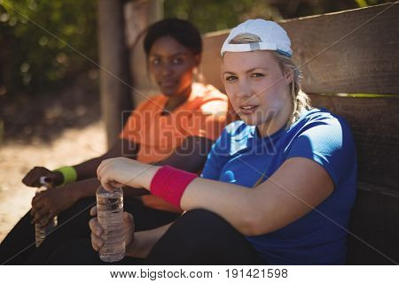 Portrait of friends relaxing after workout during obstacle course in boot camp