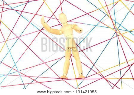 Any colorful wool threads form a network, on which a wooden doll sits.