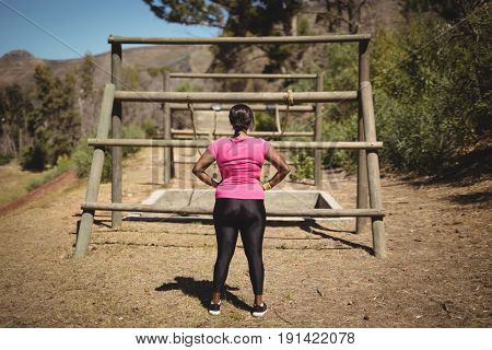 Rear view of woman looking at outdoor equipment during obstacle course in boot camp