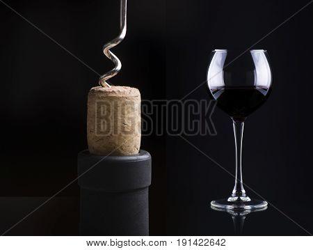 Macro shot of bottle of wine with corkscrew.