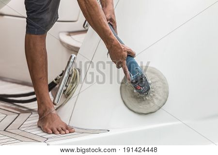 Yacht Maintenance. A Man Polishing Side Of The White Boat In The Marina