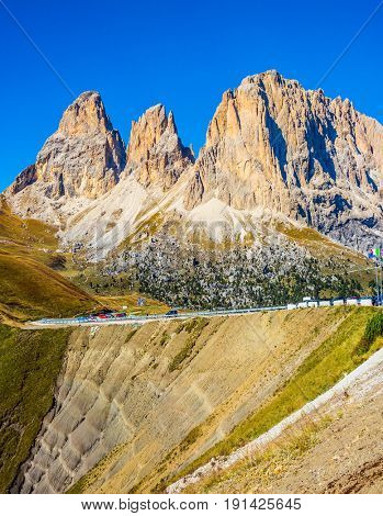Magnificent ridge of dolomite rocks on the Sella Pass, Dolomites. Picturesque road through the pass. The concept of extreme and ecological tourism