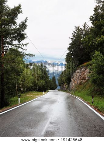 Wet shiny road in the Swiss Alps. Cold autumn day