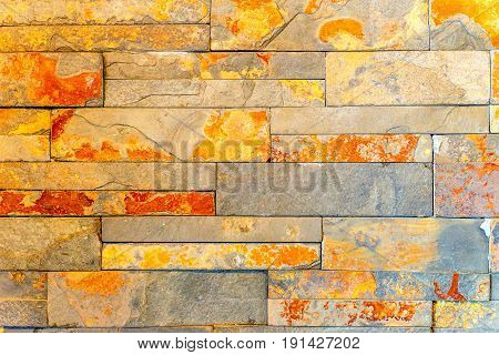 Closeup of red and orange rough modern stonewall background