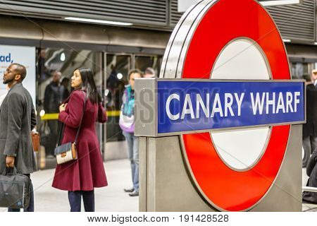 Canary Wharf Underground Sign With Commuters Waiting On A Platform In The Background