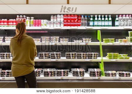 A Female Customer Browsing Cold Food Displayed On Multideck Fridges At Itsu In Canary Wharf