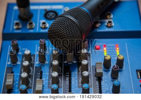 The equipment for recording. Microphone lying on sound mixing Board.