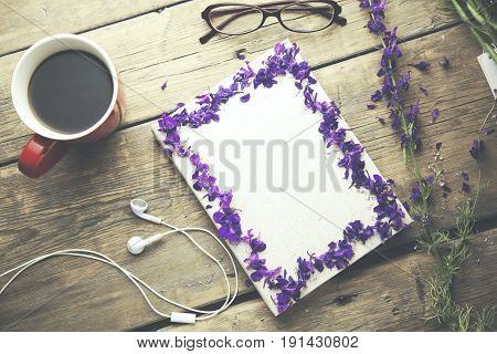 red cup of coffee on book and glasses and flower on wooden table
