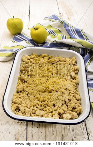 british apple crumble freshly baked in an white and blue enamel bowl