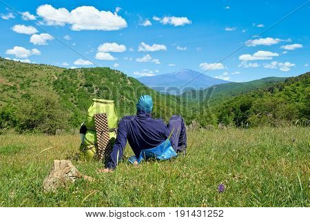 man with backpack relaxing in  Nebrodi Park with Etna Mount on background, Sicily