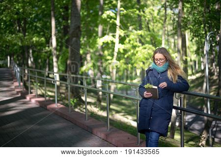 Happy girl reading a book at the railing
