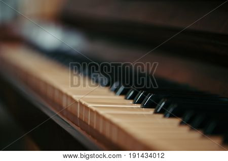 Keys of an old piano in blur. Musical ancient instrument with a wooden case. Vintage.