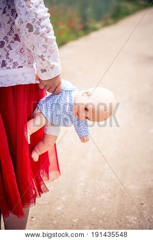 little girl in red dress with dollon the street