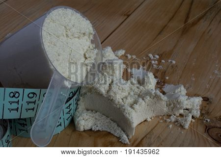 Whey protein with measuring tape on wood