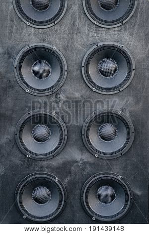 Several speaker speakers in a wooden black wall. Wall of large black music speakers.