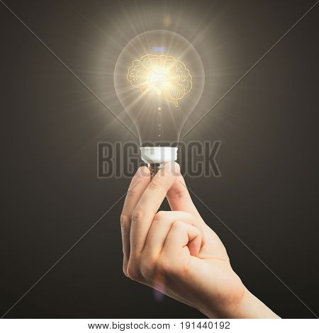 Close up of hand holding illuminated light bulb with brain on dark background. Brainstorming concept