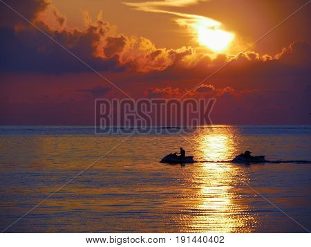 Silhouette of a man in a jet ski at sunset  A man in jet ski silhouetted against a beautiful sunset with the water displaying golden ripples