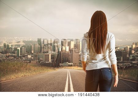 Back view of young woman on road looking at moden city. Forward concept