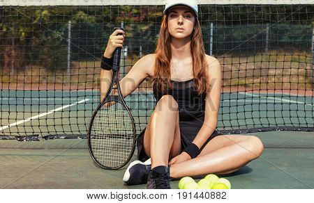 Confident Female Tennis Player Resting On Court