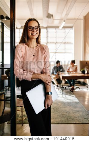 Portrait of happy female startup employees standing at office doorway with laptop. Smiling female executive at office with colleagues working in background.