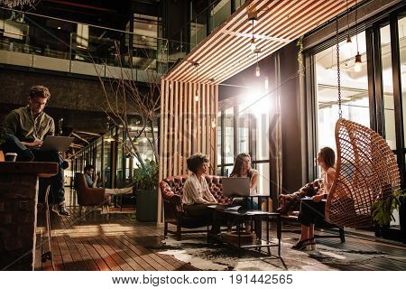 Business people sitting in social room in modern office. Young men and women taking a break from work.