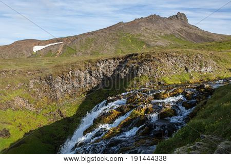 Iceland Landscape With Small Waterfall Running Among Green Hills And Rocks Covered With Bright Green