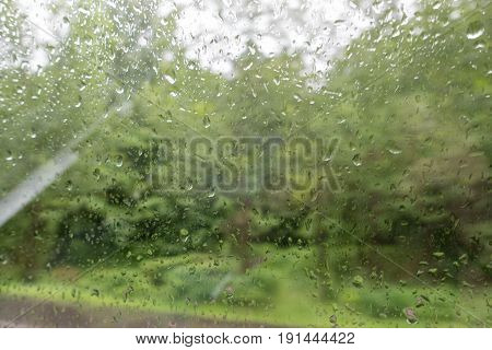 Raindrops on the windscreen of a car. Green nature bakcground
