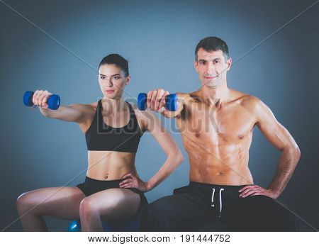 Two smiling people with fitness ball in the gym. Personal fitnes