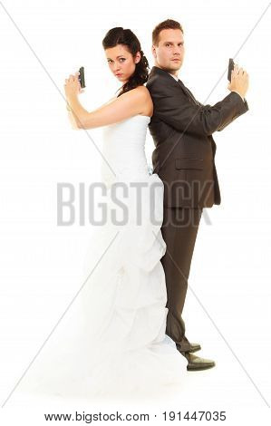 Marriage agents conflict in relationship concept. Groom and bride in wedding outfit holding guns dealing with life enemies.