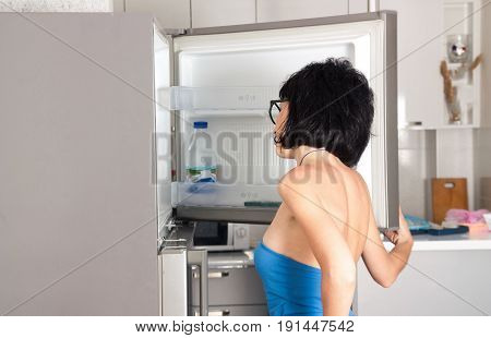 Woman looking into the fridge at home