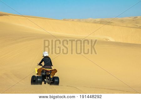 Two happy quad bikers driving in sand dunes. Young active couple in outdoor activity driving quad ATV on coastal desert beach, Africa.