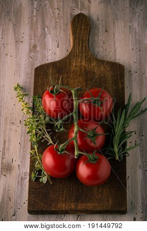 Few Red Cherry Tomatoes On Green Branch With Herbs
