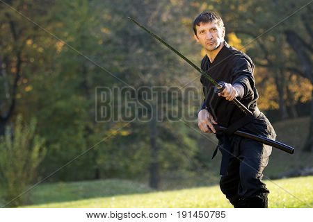 Black ninja is practicing martial arts with sword outdoors in nature.