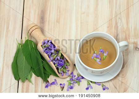 Sage herbal tea Salvia officinalis with sage leaves and flowers on wooden board