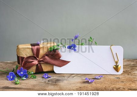 Fathers day card gift box with brown ribbon white paper tag space for text blue flowers on wooden table