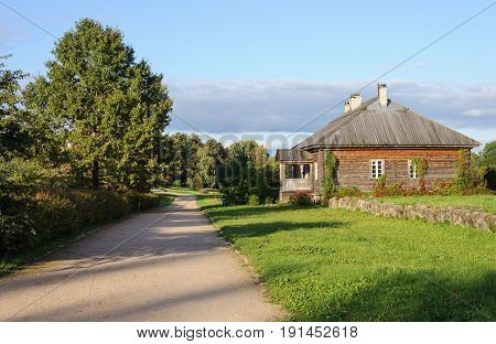 Entrance alley and wooden service house in the manor of Trigorskoye village Pushkinsky reserve Russia. Sunny summer evening.