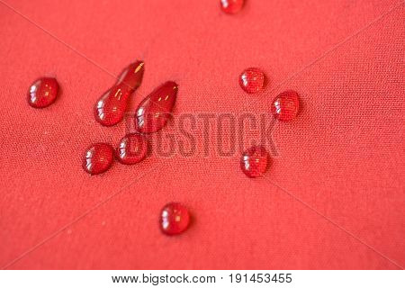 large water drops on red waterproof membrane apparel close up of texture fabric