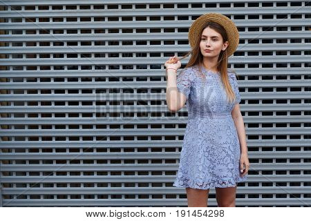 Portrait of a beautiful graceful woman in elegant hat and blue lace dress.