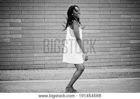 Portrait Of A Fabulous Black African American Woman Dancing And Jumping Against Brick Wall In The Ba