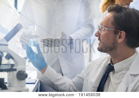 Male Scientist Working With Microscope, Team In Laboratory Doing Research, Man And Woman Making Scientific Experiments Doctors In Lab