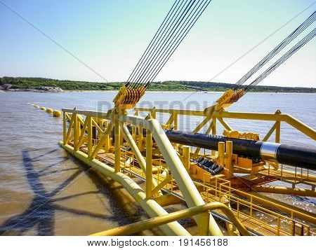 Laying Of Pipes With Pipe-laying Barge Crane Near The Shore. Descent Of The Pipeline To A Bottom Exh