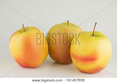 Three large ripe apples on a white background