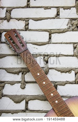 Acoustic guitar headstock against white brick wall, close up